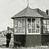 F2286<br /> De kiosk annex snoeptent van Cor van Werkhoven op Sassem-noord. Er stonden ook een paar stoelen in en je kon er koffie drinken. Bij mooi weer werden de stoelen buiten gezet. Cor van Werkhoven staat links van de kiosk. Achter de kiosk op de hoek Hoofdstraat/Ter Leedelaan is het rieten dak van het huis te zien, waar H.C. Westerbeek woonde (Hoofdstraat 304).<br /> Cor van Werkhoven woonde destijds op de 3e Poellaan. De kiosk stond op het graslandje tussen de Van Pallandtlaan en de Ter Leedelaan aan de Hoofdstraat. De kiosk heeft er tot begin jaren '50 gestaan. Op ditzelfde landje, maar dan meer naar rechts, is daarna in de jaren '50 Thomas van Kesteren met zijn patatkraam begonnen. De foto is van eind jaren '40.