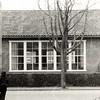 F4609<br /> Een deel van de school die in 1951 gebouwd werd aan de vijver van de Dr. De Visserlaan voor de mulo-afdeling van de Dr. De Visserschool. Het lokaal op de foto staat aan de St. Antoniuslaan; op de achtergrond zien we een deel van een huis aan de Menneweg (het deel tussen J.P. Gouverneurlaan en Parklaan).<br /> In 1959 vertrok de Dr. De Visserschool naar een nieuw gebouw aan de Menneweg nr. 12. Het gebouw op de foto werd toen betrokken door de openbare lagere school, de Kastanjehof. In 1998 verhuisde de openbare school naar  het gebouw waar nu 't Onderdak is en ging toen Het Bolwerk heten. Enige jaren later werd in het gebouw op de foto de Vrije Academie gevestigd, St. Antoniuslaan 24A. Foto:1975.