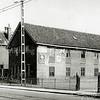 F1034 <br /> Tot 1962 was dit de werkplaats van aannemer E. Dijkstra aan de Hoofdstraat van oorsprong een bollenschuur. Aan de voorkant de werkplaats (timmerwinkel) met daarachter de karrenloods. Hierachter weer de zogeheten rasterloods waar de voorraad van hard en zacht hout was opgeslagen. Het achterste gedeelte werd gebruikt voor de kistenfabricage met opklampbank en afkortzaag (sinds 1920) en opslag van kistenhout.