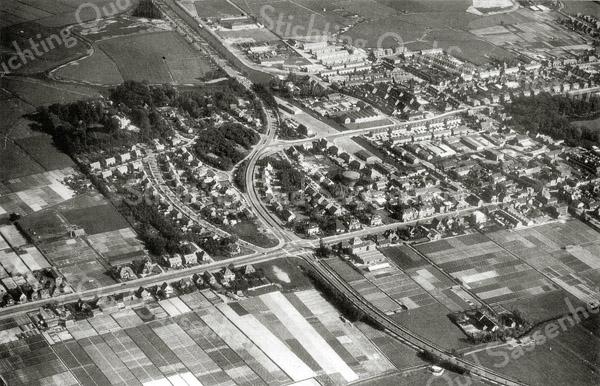 F0331 <br /> Luchtfoto van Sassenheim. De Kooiwijk is nog niet gebouwd. Van links naar rechts loopt de Hoofdstraat met kruispunt Sassenheim-noord. Rechtsonder de boerderij van Wim van Rijn. Linksboven buitenplaats Ter Leede (in het bos) met de Ter Leedelaan. In het midden is de gashouder aan de Molenstraat te zien. Middenboven de Sassenheimervaart met de Industriekade. Verder in het midden het kruispunt Van Pallandtlaan en de Parklaan. Uiterst rechts het park Rusthoff. Foto: jaren '60.