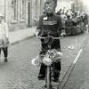 F4398<br /> Albert (Appie) Vos rijdt hier bij de diaconiehuisjes aan de Hoofdstraat tussen Melman en Bakker Buijs op zijn versierde fiets tijdens een kinderoptocht.