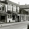 F1659 <br /> Hoofdstraat, gezien naar het zuiden. Links de slagerij van Corn. P. van der Meij; daarnaast bakkerij Wanninkhof; het huis van C. Stelma; het huis van de fam. C. Melman; de damesmodezaak van P.C. Melman en de schoenwinkel van A. Witte.  De lage huisjes werden eind  jaren '70 gesloopt. Foto: 1976.