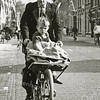 Postbode Klaas Kuperus met zijn zoon voorop de transportfiets. Ze rijden op de Hoofdstraat, ter hoogte van het Postkantoor.
