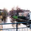 F0324 <br /> Gezicht op de Sassenheimervaart vanaf de brug in de Concordiastraat. Rechts de plek waar vroeger het buurtje Weltevreden stond. Thans staan daar wooncaravans, compleet met schuren en tuintjes. Op de achtergrond de vroegere bollenschuur van B.D. Kapteyn & Zn. Links de bedrijfsruimte van Noort Elektrotechniek BV. Helemaal op de achtergrond de achterkant van bouwbedrijf M.J. van Breda & Zn. aan de Kerklaan. Foto: 1998.