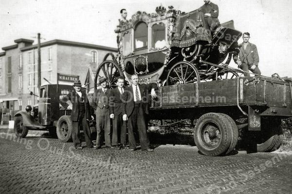 F0394 <br /> De gouden koets wordt op een vrachtwagen getransporteerd. Achter de vrachtwagen de bollenschuur van W.J. Eldering & Zn. Bovenop de bok van de koets zit een begeleider. Foto: 1938.