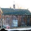 F0138 <br /> Dit is de achterzijde (westkant) van de gereformeerde kerk aan de Hoofdstraat. Let op de dichtgemetselde gotische ramen.  Foto: 1990.