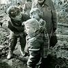 F1501<br /> Mej. W.J.M. van der Eerden, onderwijzeres aan de r.-k. meisjesschool St. Anna van 1943 tot 1972. Daarna was zij nog vele jaren op deze school actief. Deze foto is genomen bij het slaan van de eerste paal voor de bouw van de nieuwe r.-k. basisschool De Overplaats op 5 maart 1985. Zij deed dit samen met de jongste kleuter Judith van Kesteren. Ook aanwezig: jonger broertje Bas en hun moeder.