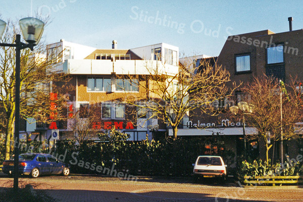 F0493a <br /> Het winkelcentrum van Sassenheim aan de Hoofdstraat met een afgebakend voetgangersgebied en de omleiding voor het autoverkeer langs de Ned.-herv. kerk of Dorpskerk. Thans is de bestrating geel en grijs gekleurd, gescheiden door een rij banken. Foto: 1999.