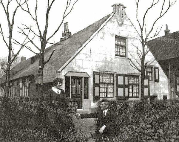 F0421 <br /> Geretoucheerde foto uit 1932 van de voormalige boerderij Wiltrijk aan de Hoofdstraat. Hier nog voorzien van de oorspronkelijke luiken en met getraliede ramen voor de deur.Toen nog bewoond door de fam. Dirk Zwetsloot, afgebeeld op de voorgrond. De achterliggende stal diende als opslag van bloembollen. Het pand rechts is het vroegere zomerhuis en is hier ook in gebruik voor de bollenteelt. Foto: 1932.
