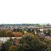 F3712<br /> Dit beeld krijgen we te zien vanuit de toren van de St. Pancratiuskerk. De hoge bomen ontnemen het zicht op de huizen van de Parklaan, de St. Antoniuslaan en Parkweide. Ook de aansluiting op de Narcissenlaan bevindt zich achter de bomen. Overigens zijn er plannen om van deze aansluiting een rotonde te maken. De woonwijk op de achtergrond is het Mennepark. Links op de voorgrond zien we het wooncomplex Parkstate. Het hoge gebouw erachter is Parkhove, dat op de plaats van de voormalige Schutse staat (hoek Menneweg/Parklaan. Foto: 2014