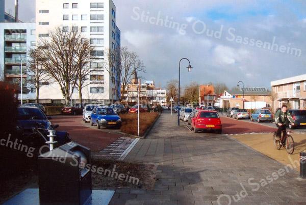 F2382<br /> Gezicht vanaf de hoek Menneweg/Rusthofflaan richting Parklaan. Op de achtergrond de kerktoren van de St.Pancratiuskerk, schuilgaand achter het appartementencomplex De Hooge Wei, waarvan de naam herinnert aan de vroegere bollentuin van Baartman & Koning. Het hoge gebouw geheel links is het appartementencomplex Parkhove. Rechts een aantal woningen en het garagebedrijf van Borst en Zn. Foto: 2011.