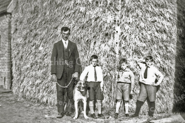 F0921 <br /> Jacob Oudshoorn, de olieman met zijn hond Hector voor de hooiberg van Willem van Rijn aan de Boschlaan. In het midden staan twee neefjes. Helemaal rechts staat Klaas Oudshoorn, zoon van Leen Oudshoorn die op de Boschlaan woonde. Links de koeienstal van Van Rijn. Foto: ca. 1934.