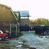 F0296 <br /> Na de sloop van de boerderij van Willem van Rijn aan de Boschlaan bleef de stal nog enige tijd staan. De voormalige olieschuur van Jacob Oudshoorn is dan al gesloopt. Rechts het buurtje van zes huizen aan de Boschlaan. Linksachter de schuur en hooiberg van Gerrit Molenaar. Het park Rusthoff op de achtergrond.  Foto: ca. 1975.