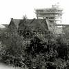 F1017 <br /> De kantoorflat van Schulte & Lestraden aan de Parklaan in aanbouw. De vlag is in top, dus het hoogste punt is bereikt. De flat is ontworpen in 1959 door de architect ir. A.H.J. Paardekooper en is in 1999 gesloopt. De foto is genomen vanaf Willem Warnaarlaan 36, vanuit het raam. Foto: ca. 1960.