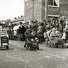 F2317<br /> Een zeepkistenrace in de Gladiolenstraat, hoek Freesiastraat.<br /> Links in de zeepkist zijn Robbert-Jan Bakker en Henk Witte (zittend in de zeepkist), geheel rechts zijn de gebroeders Quarree (tweeling). De foto is genomen in 1958/59. Op de foto is de man met hoge hoed op Niek Dofferhoff in zijn functie als lid van het Oranjecomité. De persoon rechts van het midden precies voor de lantaarnpaal is meester Nijholt van de hervormde school. De vrouw voor meester Nijholt is Truus Dofferhoff. Links is ook nog dhr. Perfors van het Oranjecomité te zien.<br /> .