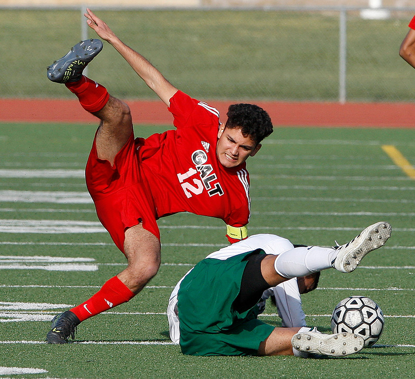 . Galt High School\'s Arath Chavez (12) gets tripped up by Alisal High School\'s Jesus Ochoa (19) during their CIF Nor Cal soccer match in Salinas on Tuesday, March 6, 2018.  Alisal High beat Galt High 3-2 to advance to the Nor Cal semifinals.  (Vern Fisher - Monterey Herald)