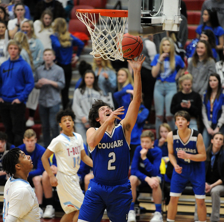 . Jackson Romero splits two defenders for a layup on his way to a team-high 22 points during Resurrection Chrisitan\'s loss to Manual.