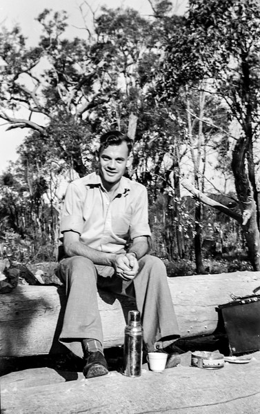 Man On Log With Thermos