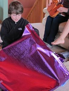 Joe opens his presents on his 8th birthday.