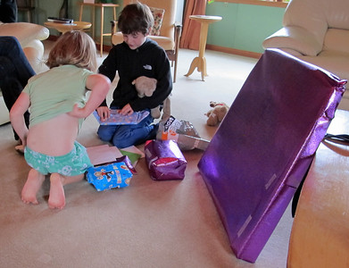Joe opens his presents on his 8th birthday.  The big purple one is a cool archery set.