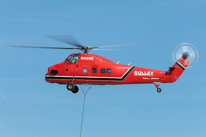A Sikorsky S-58ET hovers over a building as it lowers air conditioning units onto the roof.