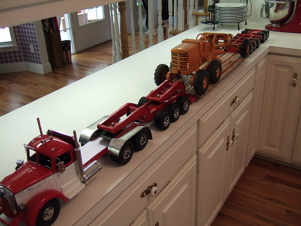This is a custom Lowboy that is available with a Jeep, Gooseneck, 19-inch deck, deck extension, rear axle unit with 4 axles, and a 2 axle Booster.  These are usually available in red, white, yellow and black.  The wooden deck is red oak.