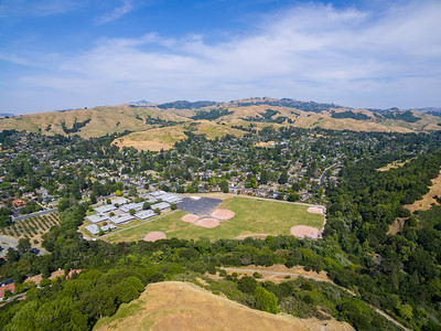 "Aerial Scenery. Joaquin Moraga Intermediate School & Moraga, CA. East Bay MUD Park at Valle Vista Staging Area - Moraga, CA, USA  Please note that the operation of aircrafts and quadcopters are not allowed in East Bay MUD parks (at least at the time these photos were taken). I was not aware of this rule when I performed this flight and I didn't see the rule posted anywhere when I arrived at the park.   Here is the entire story for that day. I saw this park and huge lake on Google Maps and thought it would be a great spot to fly. At the time, I was not aware that the ""lake"" is actually the Upper San Leandro Reservoir. If I had known that, I would not have done the flight. I also saw that it was not a East Bay Regional Park, which I know has banned the operation of quadcopters and remote aircrafts. I did take a general look around after I arrived at the staging area, but didn't notice any signs that banned quadcopters so I thought I was in the clear. Around the same time, East Bay Regional Park Police and a park ranger were called in for some other stuff. Either way, they saw me bring my quadcopter into the park. I set up my quadcopter at a picnic table and waited for several minutes to see if one of them was going to come talk to me about a rule I might not have been aware of. They did eye me a few times and I eyed them a few times but they didn't come over. By that point, I thought it was fine and started my flight. It wasn't until after I finished my flight and packed away my quadcopter that a East Bay Regional Park Police officer came to talk to me. He told me that I wasn't suppose to fly my quadcopter here and said that he's letting me off with a warning.   I would like to thank the ranger that day and the East Bay Regional Park Police for helping me learn the rules of the park and for being kind enough to let me off with a warning. I won't do this again in East Bay MUD parks as long as the rule is in place. With this in mind, if any one running the East Bay MUD parks, rangers, or East Bay Regional Park Police would like a copy of any of these aerial photos I took in this East Bay MUD park for publications, websites, etc..., contact me and I'd be happy to provide a high resolution copy for use as a show of gratitude.   As for everyone else reading this, I would also like the following to be known. I've been diagnosed with generalized anxiety issues. Getting in trouble or crashing my quadcopter is definitely not something I want or willing to do. I generally do a thorough look through of the area I'm going to be flying in on Google Maps before the flight. Sadly, Google Maps did not have the reservoir labeled at the zoom level I was at on the map. I do a detailed review of the satellite imagery of the area I'm going to be flying in before my flights to check for potential obstacles & hazards (such as high voltage power lines). I also check distances during my planning and conservatively calculate how far I'm willing to fly my quadcopter and attempt to factor in wind resistance that might be expected on the day of the flight. When I get to the area I'm going to fly in, I also spend some time looking around before the flight to check for potential obstacles. During my flights, I generally only fly forward so I can see what is in front of the quadcopter by the video feed. Now and then, I will do a 360° spin around to check for other potential obstacles. During my flight, I also keep a constant watch on my battery power, flight speed, distance, and other factors. I take many precautions before and during my flights to ensure the flight is done safely."