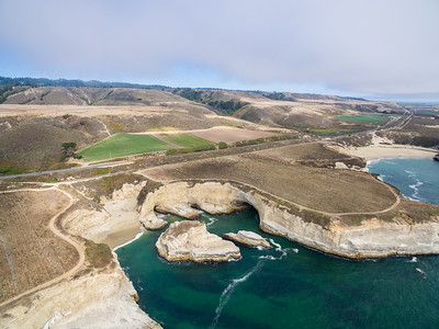 Aerial Scenery. Shark Fin Cove - Davenport, CA, USA  The beach is also known as Shark Tooth Cove, Shark Tooth Beach, Shark Fin Beach, and Davenport Cove. In the distance on the right is Bonny Doon Beach in Santa Cruz, CA.
