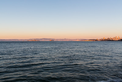 Sunset. Alcatraz Island (Left), Bay Bridge (slightly right from center), and Downtown San Francisco (Right). Near Torpedo Wharf - Presidio - San Francisco, CA, USA