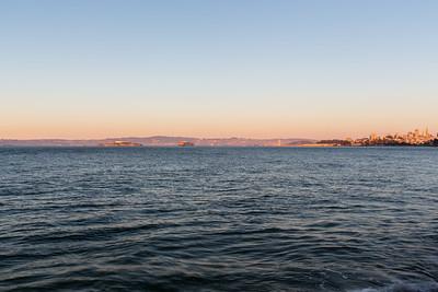 Sunset. Alcatraz Island (Left), Bay Bridge (slightly right from center), and Downtown San Francisco (Right). Near Torpedo Wharf - Presidio - San Francisco, CA, USA