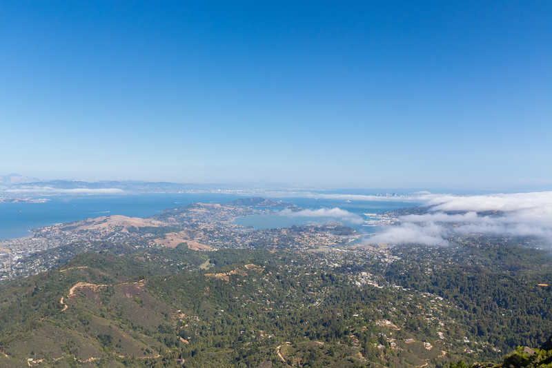 Marin Headlands with Oakland, San Francisco, CA, and Bay Bridge (in the distance behind clouds).<br /> <br /> Also in the photo in the center is Angel Island State Park (slightly left) & Alcatraz Island (slightly right).<br /> <br /> Photo shot on East Peak near or along the trail up to East Gardner Fire Lookout. Mt. Tamalpais State Park - Marin County, CA, USA