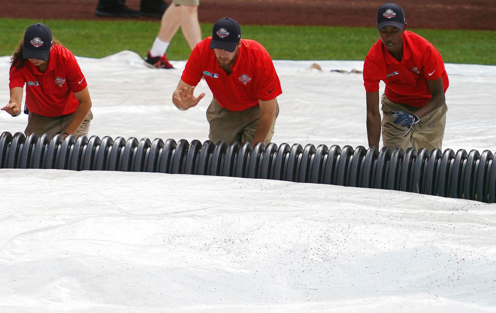 . Ground crew work tarps ahead of the 89th MLB baseball All-Star Game, Tuesday, July 17, 2018, at Nationals Park, in Washington. (AP Photo/Carolyn Kaster)
