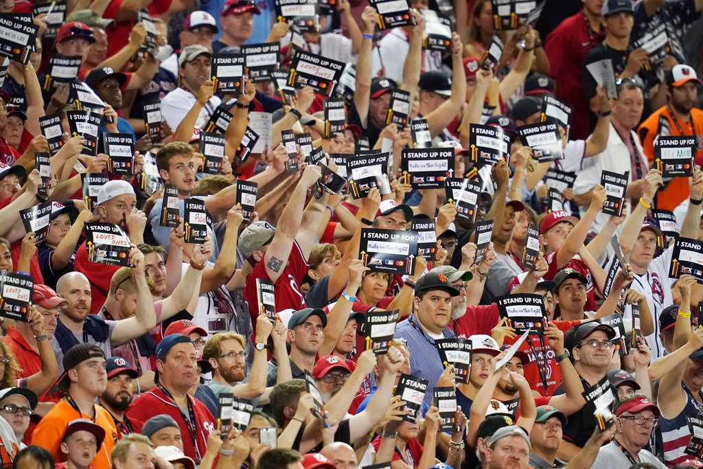 . Fans stand with anti-Cancer signs during the 89th MLB baseball All-Star Game, Tuesday, July 17, 2018, at Nationals Park, in Washington. (AP Photo/Carolyn Kaster)