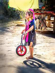 """Playful Kayan girl highlighted by the late afternoon sun. When I visit other cultures, the site of children playing is often the most heartfelt reminder of similarities we all share. In the Kayan culture, some of the women wear brass rings around their neck (as seen in this picture), and so this tribe is also known as the """"long neck"""" tribe.  Baan Tong Luang Hill Tribe Village, Thailand"""