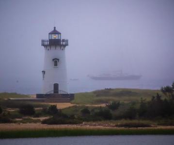 Sailboat passing the Edgarton Lighthouse on a foggy morning off Martha's Vineyard, Massachusetts