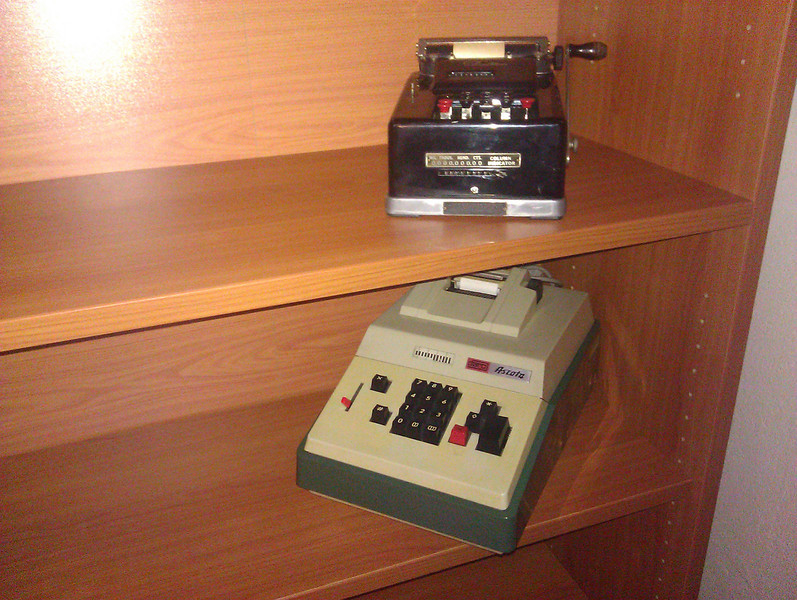 two vintage adding machines, hand crank on top, underneath is an electrical, both with rotor calculator mechanisms