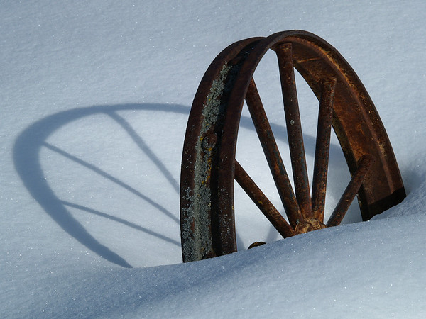 Iron wheel casting an early morning shadow.