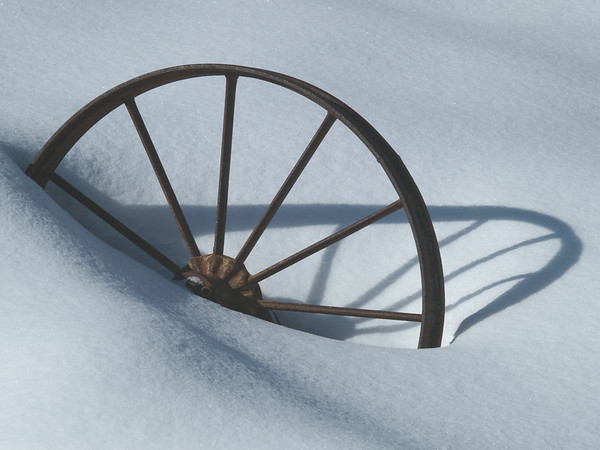 Iron wheel casting a mid day shadow.