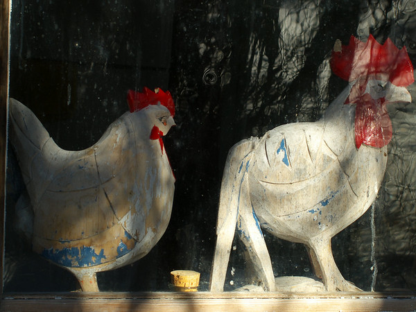 Wooden Chickens in an old farm house window.