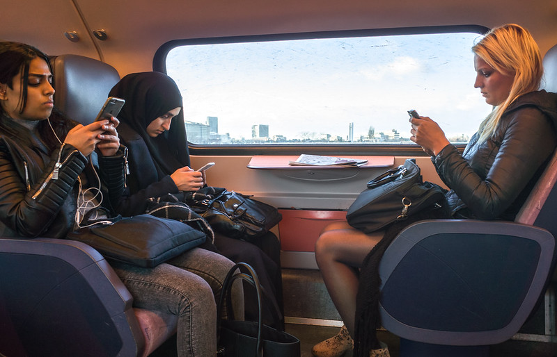 16 January 2017: three young Dutch women, obviously with different backgrounds and cultures, doing the same thing on the Schiphol-Den Haag train.