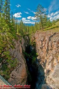 Blue skies over deep dark limestone gorge of the Maligne River Canyon within Jasper National Park (Canada Alberta Jasper)