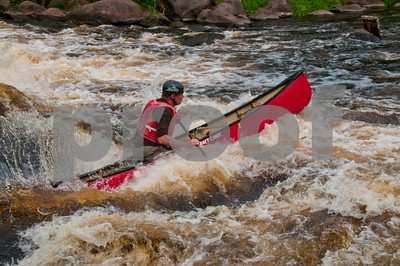 Courageous veteran canoeist Charlie Frisk expertly back-surfing his open canoe in a white water curler of Gilmore's Mistake Rapids on the wild Wolf River (USA WI White Lake)