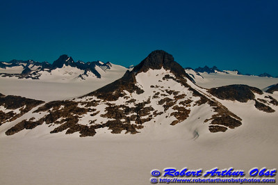 Winter during summer: Cerulean skies embrace the Juneau Icefield and its snowy mountain peaks and snowfields within the Tongass National Forest during - can you believe it - July (USA Alaska Juneau)