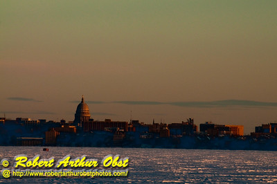 Orange sunset over State of Wisconsin Capitol of Madison encircled by ice and snow on Lake Mendota and Lake Monona from Governor Nelson State Park (USA WI Waunakee)