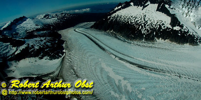 Ambitious hikers and ice climbers and float plane riders can enjoy blue sky views of remote snowy mountains and flowing rivers of ice from near the top of twelve miles long Mendenhall Glacier within Tongass National Forest (USA Alaska Juneau)