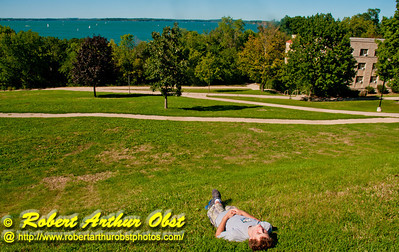 Youth soaking up the warmth and freshness of a perfect summer day under blue skies on the University of Wisconsin Madison campus by Obervatory Drive along Lake Mendota (USA WI Madison UWM Observatory Drive by Lake Mendota)