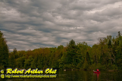 Beautiful brooding spring skies over canoeist on Section 3 of the wild Wolf River between Langlade and Twenty Day Rapids (USA WI White Lake)