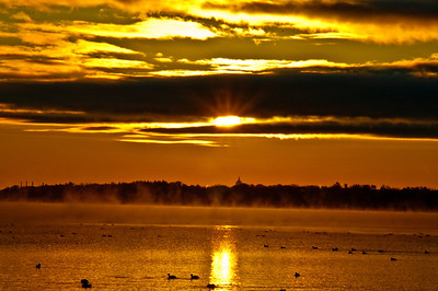 Brilliant orange sunrise over Lake Mendota and the State Capitol of Madison Wisconsin from Pheasant Branch Conservany (USA WI Middleton)