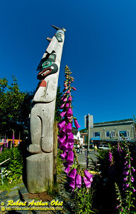 Cerulean skies and violet flowers profile Chief Kyan Totem Pole in Whale Park within downtown Ketchikan (USA Alaska Ketchikan)