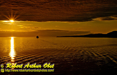 """Holland America Zaandam cruise ship passengers on the way to Alaska enjoy a spectacular orange """"midnight"""" sunset within the Inside Passage of British Columbia Canada (CAN BC Inside Passage Vancouver)"""